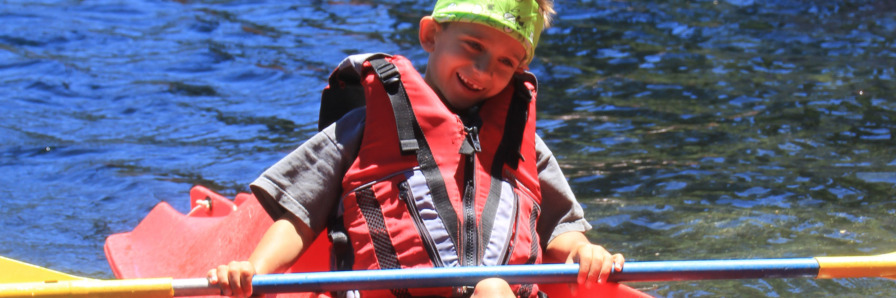 A young child kayaking on a lake